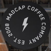 The Madcap Coffee sign, with its distinctive lightning bolt symbol, hanging from the roof at Grand Rapids' Downtown Market.