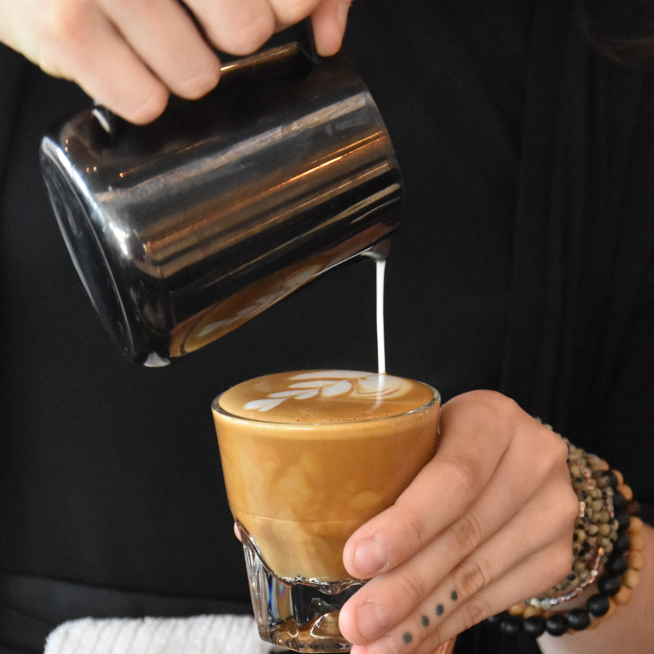 Pouring latte art at Madcap Coffee, Downtown Market in Grand Rapids, Michigan.