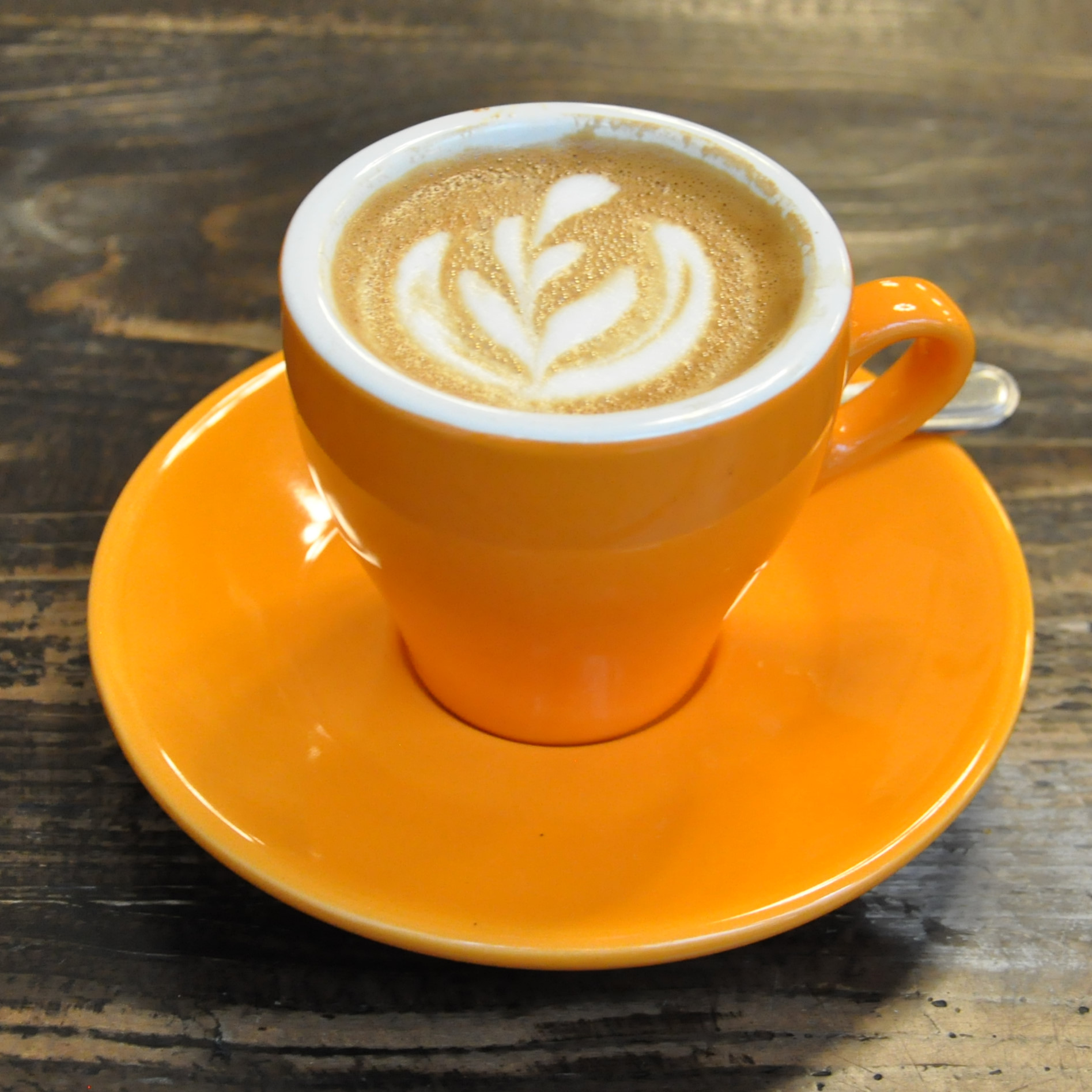 A flat white from Café Grumpy, in an orange, six-ounce tulip cup.