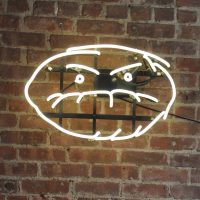 Cafe Grumpy's grumpy face logo, hanging on the wall of the Lower East Side branch.