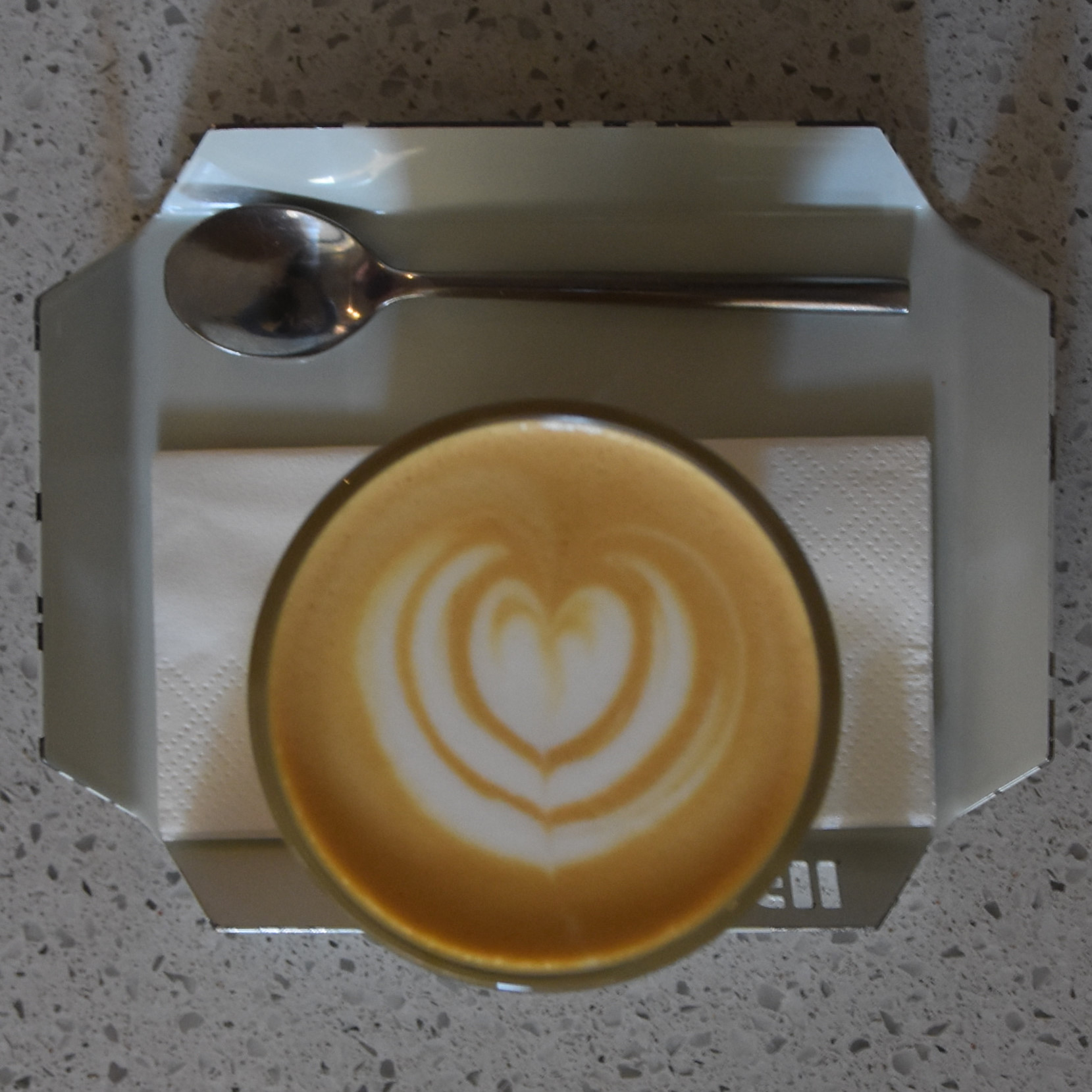 A lovely flat white from Pauseteria, served in a glass on a small, metal tray, and made with an Ethiopian single-origin roasted by Candy Cane.
