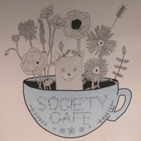 The mural on the wall of the basement in Society Cafe, The Corridor, in Bath, showing flowers growing in a coffee cup, with a small animal peaking its head out.