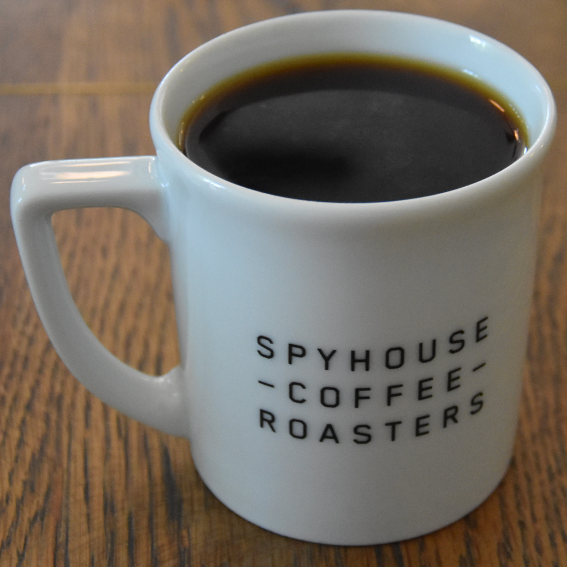A white diner mug, with Spyhouse Coffee Roasters written on the side, containing my batch-brew, a Vincente Diaz single-origin from El Salvador,