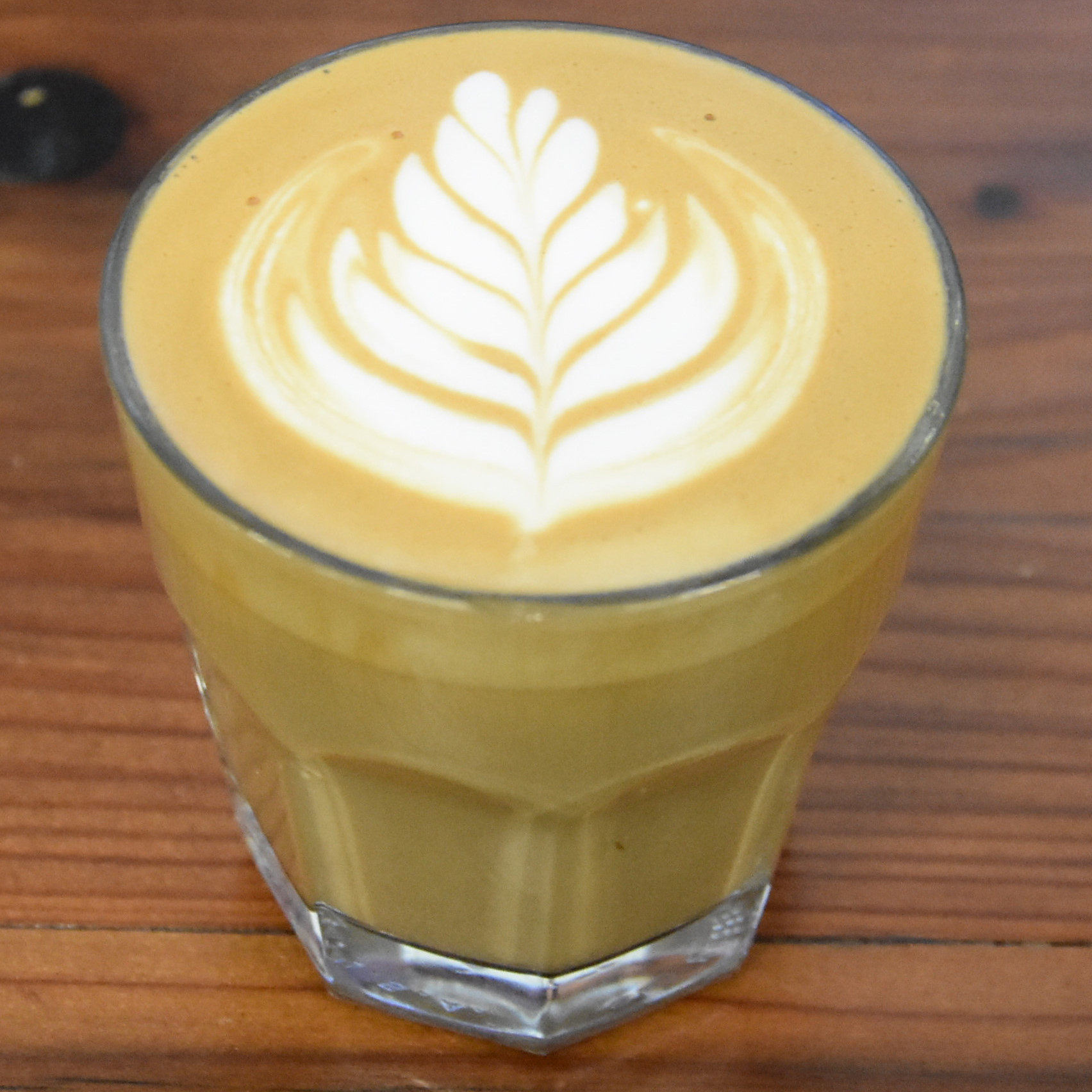 My flat white, in a glass, at the Chromatic Coffee Roastery Cafe in San Jose.