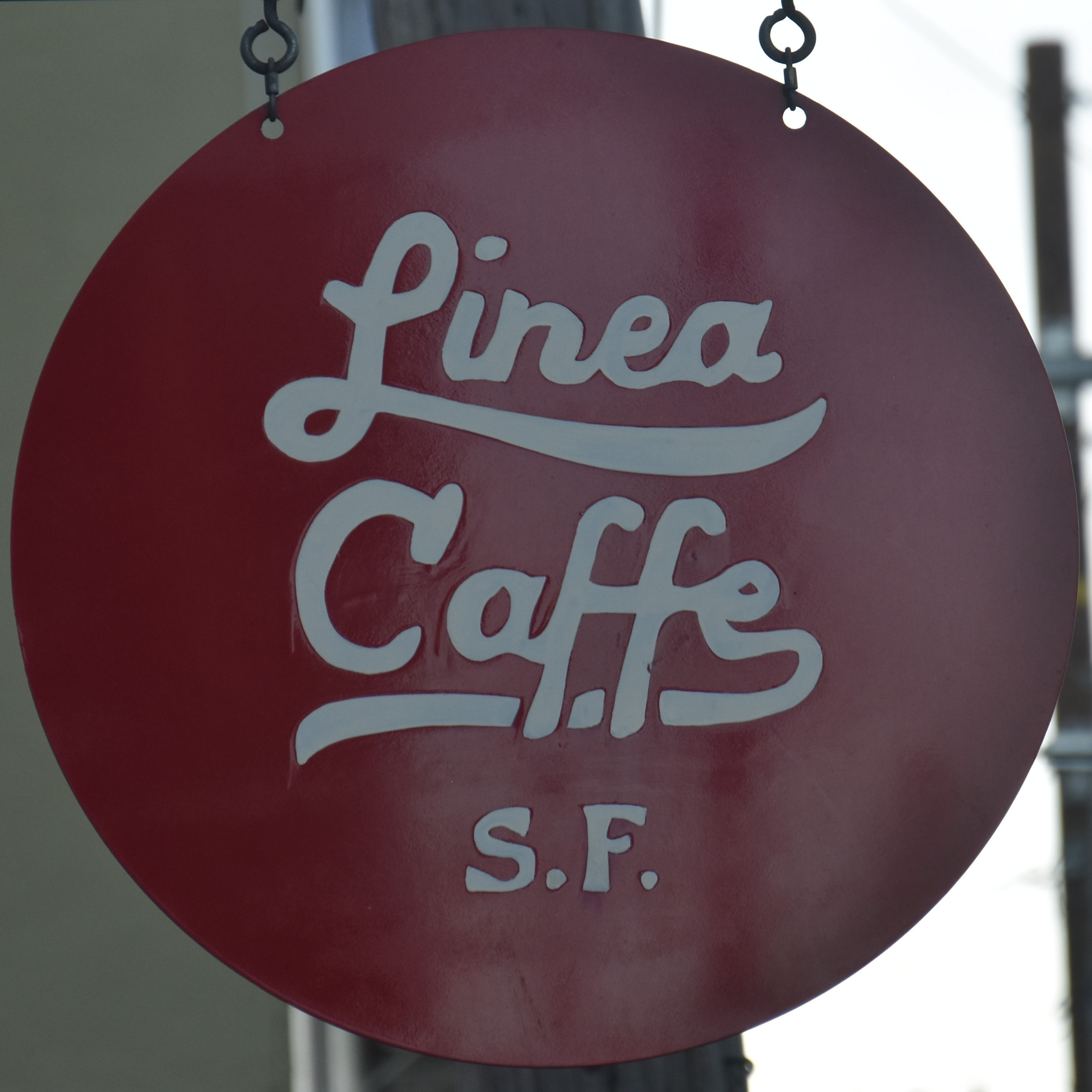 """The Linea Caffe sign, from my visit in April 2019, with the words """"Linea Caffe S.F"""" written in white in a cursive script on a red, circular background."""