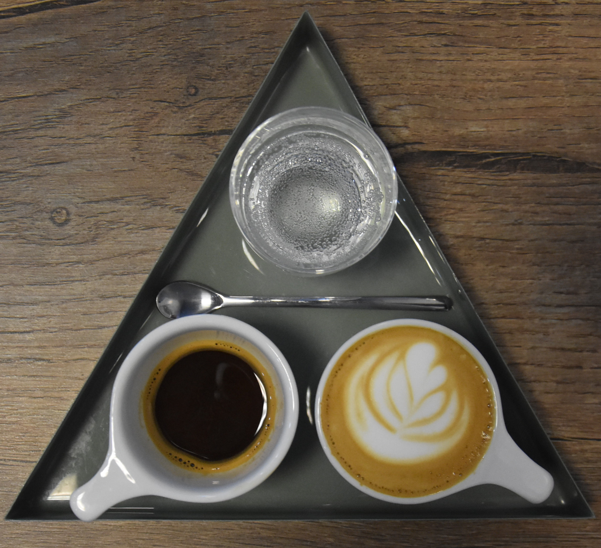 A lovely one-and-one (espresso and macchiato) plus a glass of sparkling water, beautifully presented on a triangular tray at Mythical Coffee in Gilbert, Arizona.