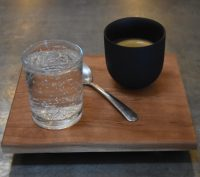 My espresso, a Colombian Geisha, roasted and served at Pair Speciality Coffee & Tea in Mesa, and presented on a square, wooden tray with a glass of water on the side.