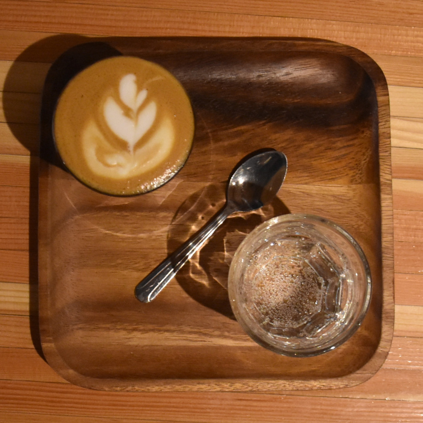 My cortado, made with the La Esperanza Colombian single-origin, roasted on-site and served in a glass, on a wooden tray, with a glass of water at the side.