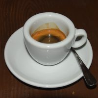 A washed Colombian espresso from Rebel Bean, served in a classic white cup at Coffee and Riot in Prague.