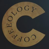 "Details of the Coffeeology logo (a letter C with the word ""Coffeeology"" written on it) from the sign hanging outside the original coffee shop in Richmond."