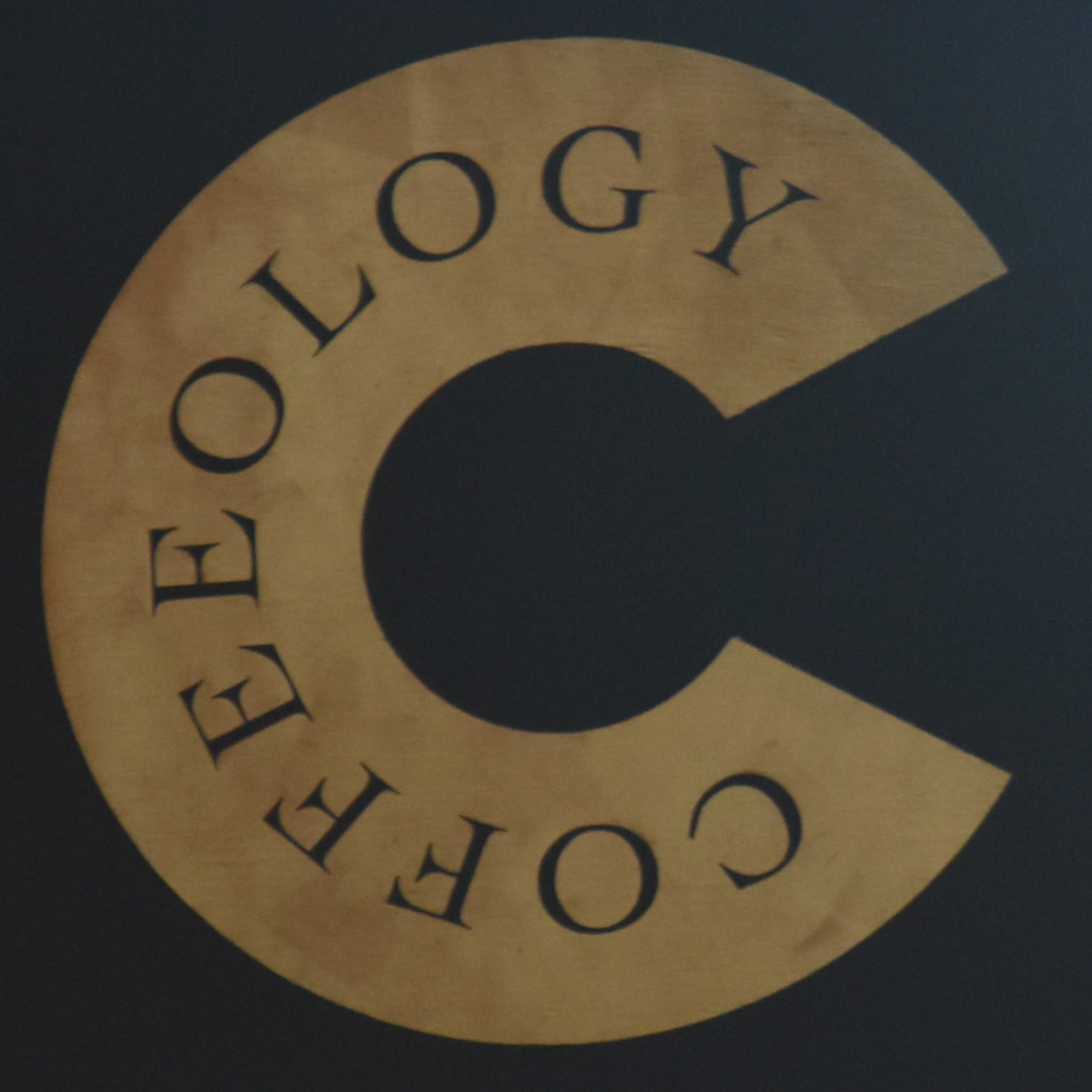 """Details of the Coffeeology logo (a letter C with the word """"Coffeeology"""" written on it) from the sign hanging outside the original coffee shop in Richmond."""