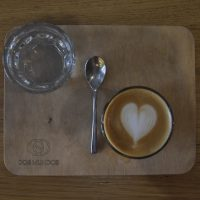 A flat white, made with a San Rafael from Honduras, one of two daily single-origins on espresso at Dos Mundos in Prague. Served in a glass, it's presented on a wooden tray with a glass of water on the side.