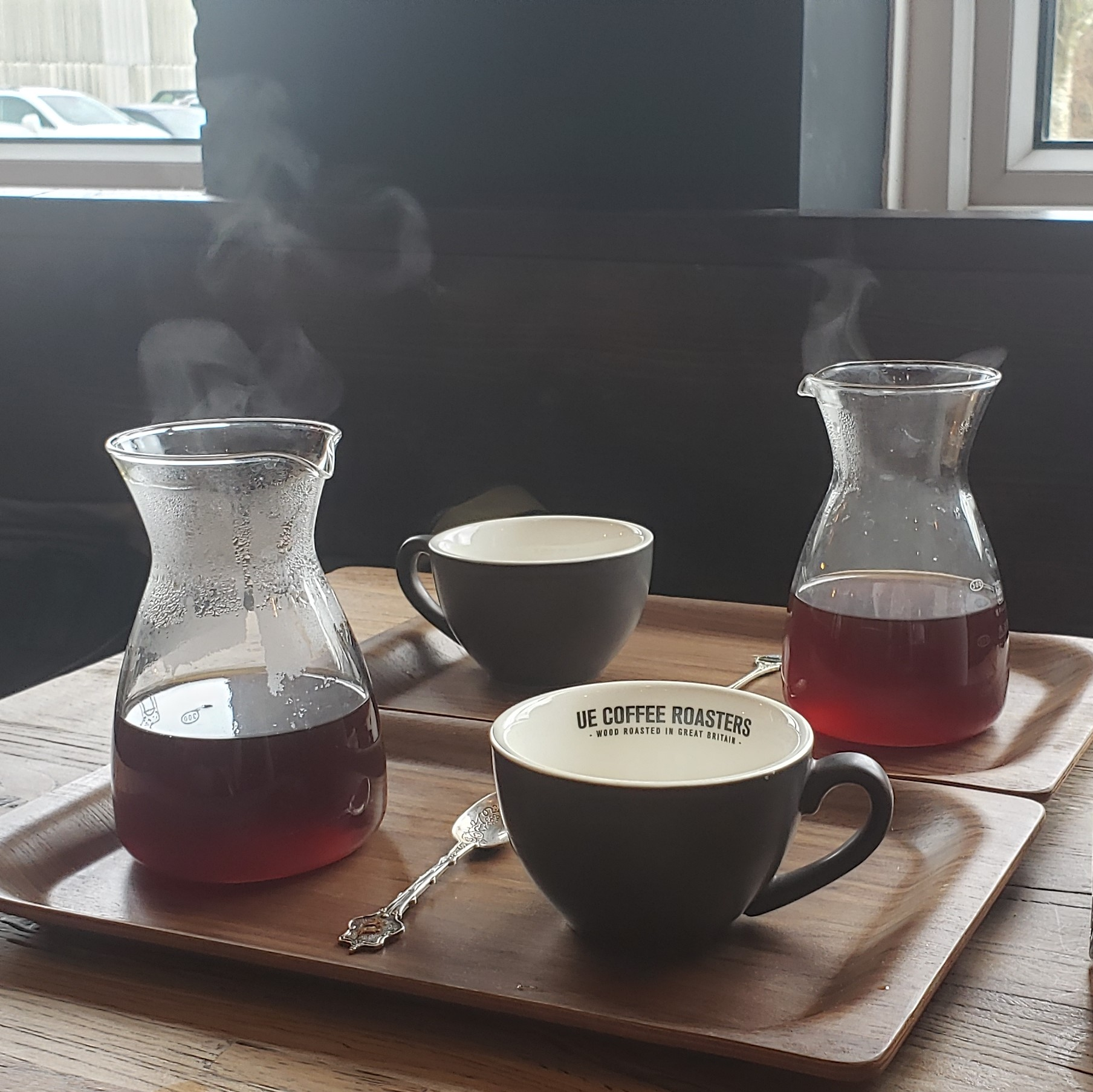 A pair of pour-overs sitting on a table in the window of the Ue Coffee Roasters Cafe & Kitchen in Witney, slowly steaming in the afternoon sun.