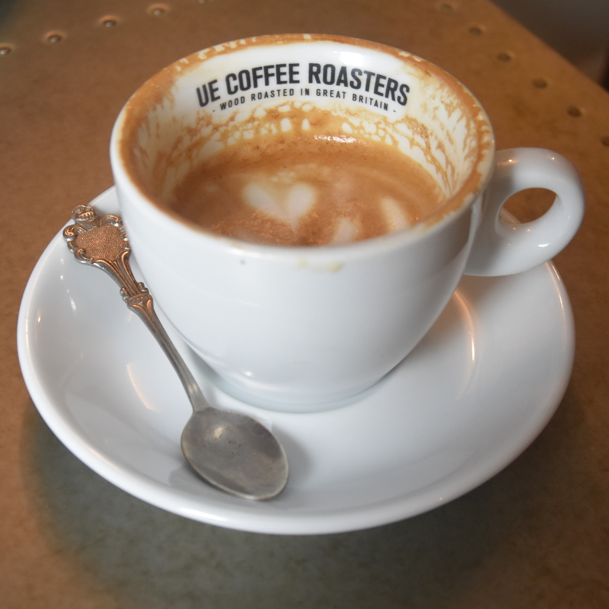 My flat white, made with the guest coffee, a washed El Salvador, and served at The Smithy, one of two Ue Coffee Roasters shops in Witney. I've drunk half of my flat white, which reveals Ue Coffee Roasters written on the inside rim of the cup.