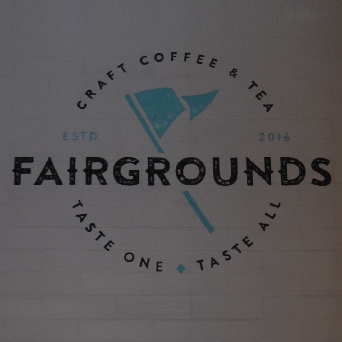 Fairgrounds, Craft Coffee & Tea | Taste One, Taste All, written on the back wall at the Bucktown location in Chicago.