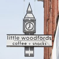 """The Little Woodfords sign, hanging outside the store on Forest Avenue in Portland, Maine. It's a design based on the clock tower which sits atop of the building and reads """"little woodfords 