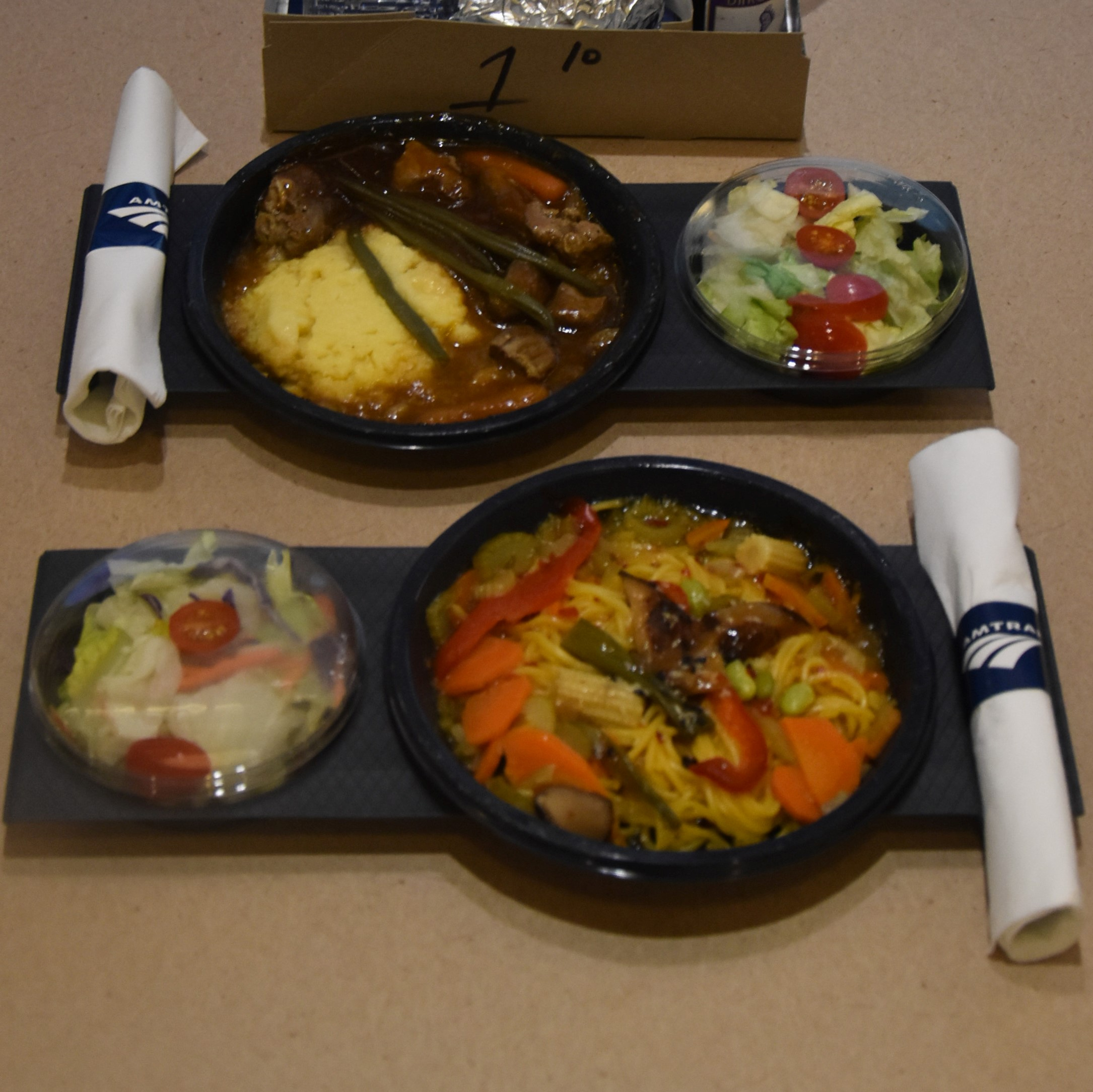 """Amtrak's new """"contemporary"""" menu on its Viewliner sleeper services: prepacked meals, delivered in a paper bag, a far cry from the full service dining cars it replaced. Bottom, my vegan Asian noodle bowl, and top, Amanda's red wine braised beef."""