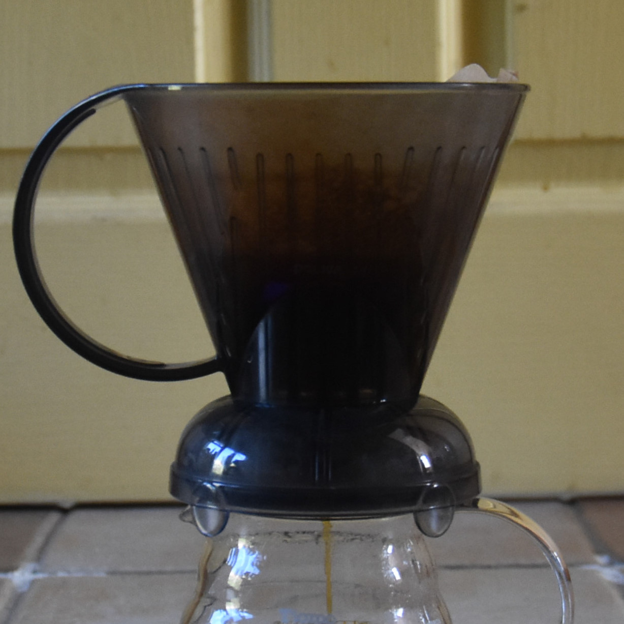 A Clever Dripper, sitting on top of a glass carafe, the brewed coffee draining through the bottom of the filter.