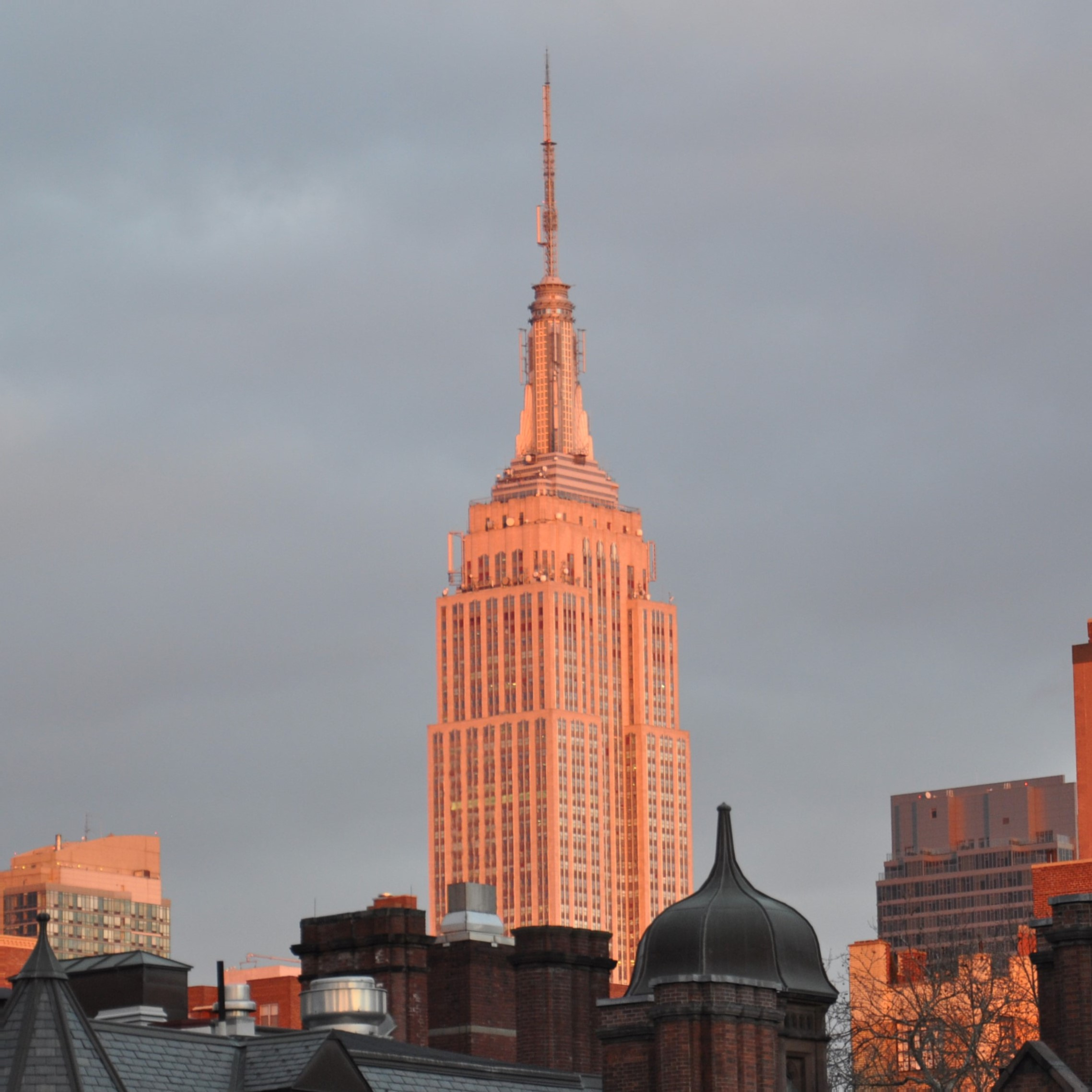 The Empire State Building seen from the Highline, rising above the Chelsea skyline and bathed in the evening sun in February 2016.