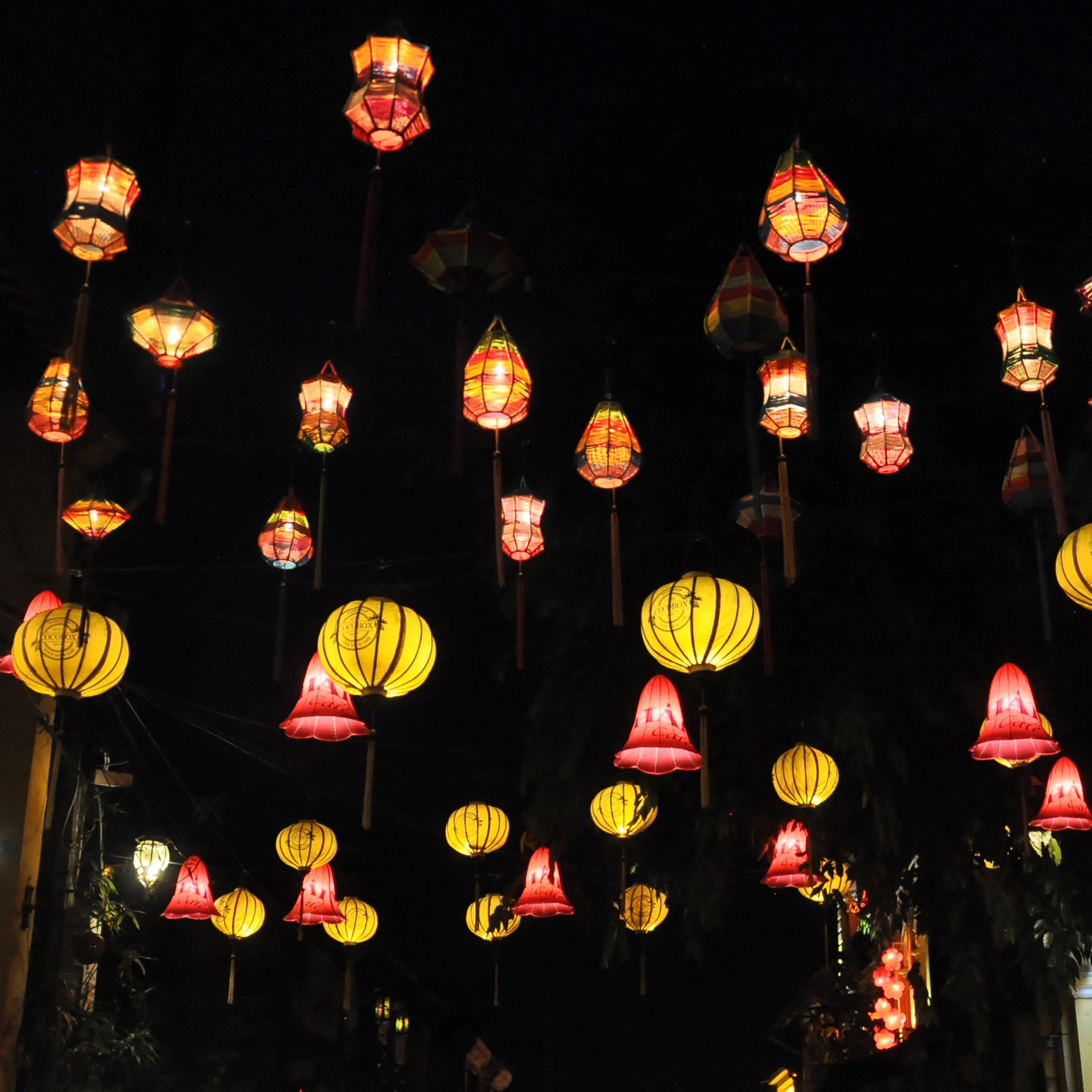 Multi-coloured lanterns hanging in a street in the Old Town in Hoi An and lit up at night.