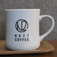 A classic white diner mug with the Nozy Coffee logo on the side