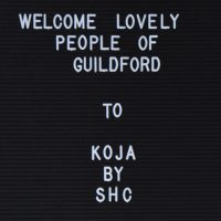 "The sign inside Koja by Surrey Hills Coffee: ""Welcome Lovely People Of Guildford to Koja by SHC"""