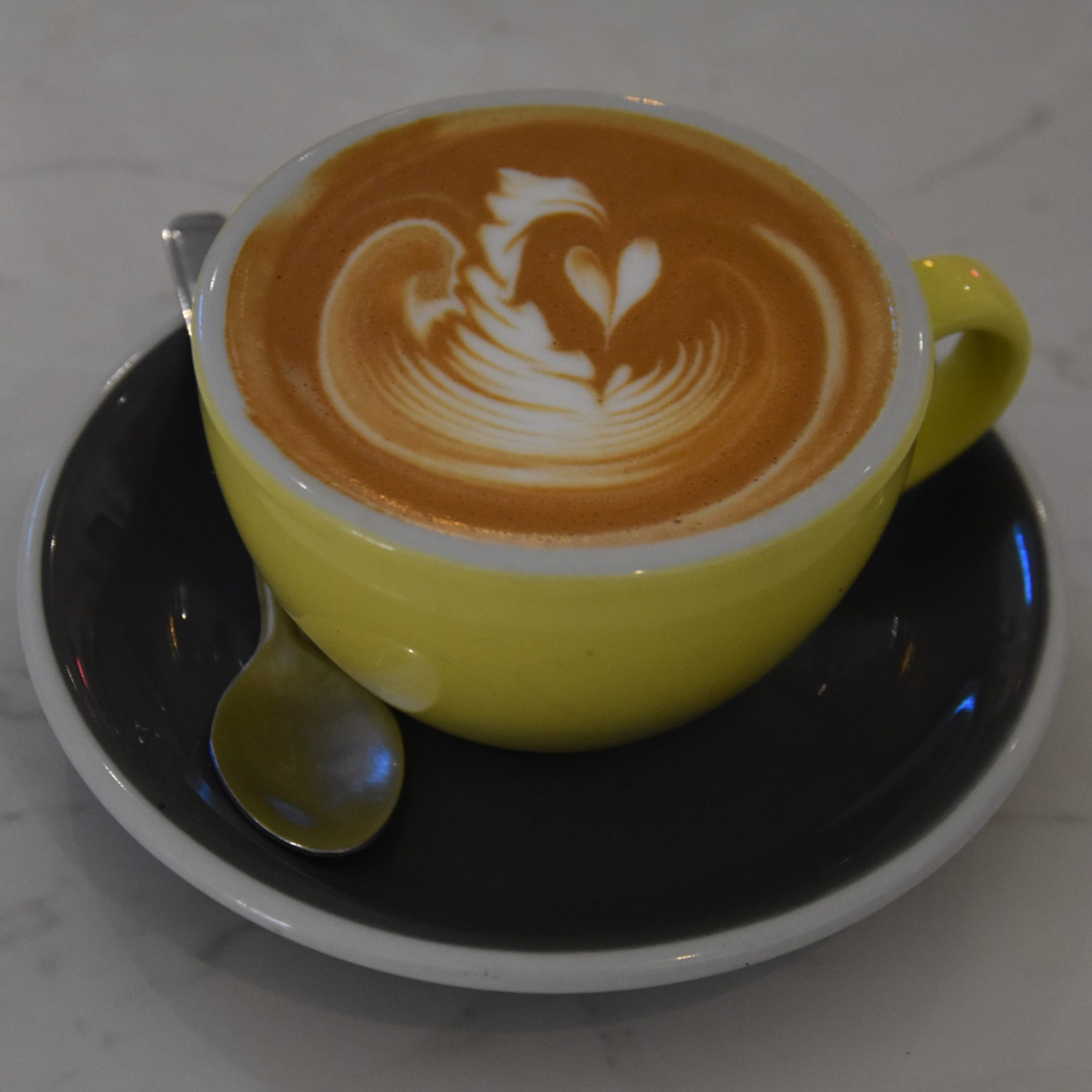 My flat white, made with a naturally-processed Brazilian single-origin from Neighbourhood Coffee, and served at The Flower Cup in a fetching yellow cup with a blue saucer and some awesome latte art.