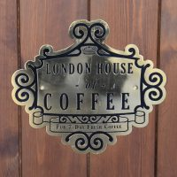 The logo of the London House of Coffee, the parent to the Ceylon House of Coffee, on the front of the counter.