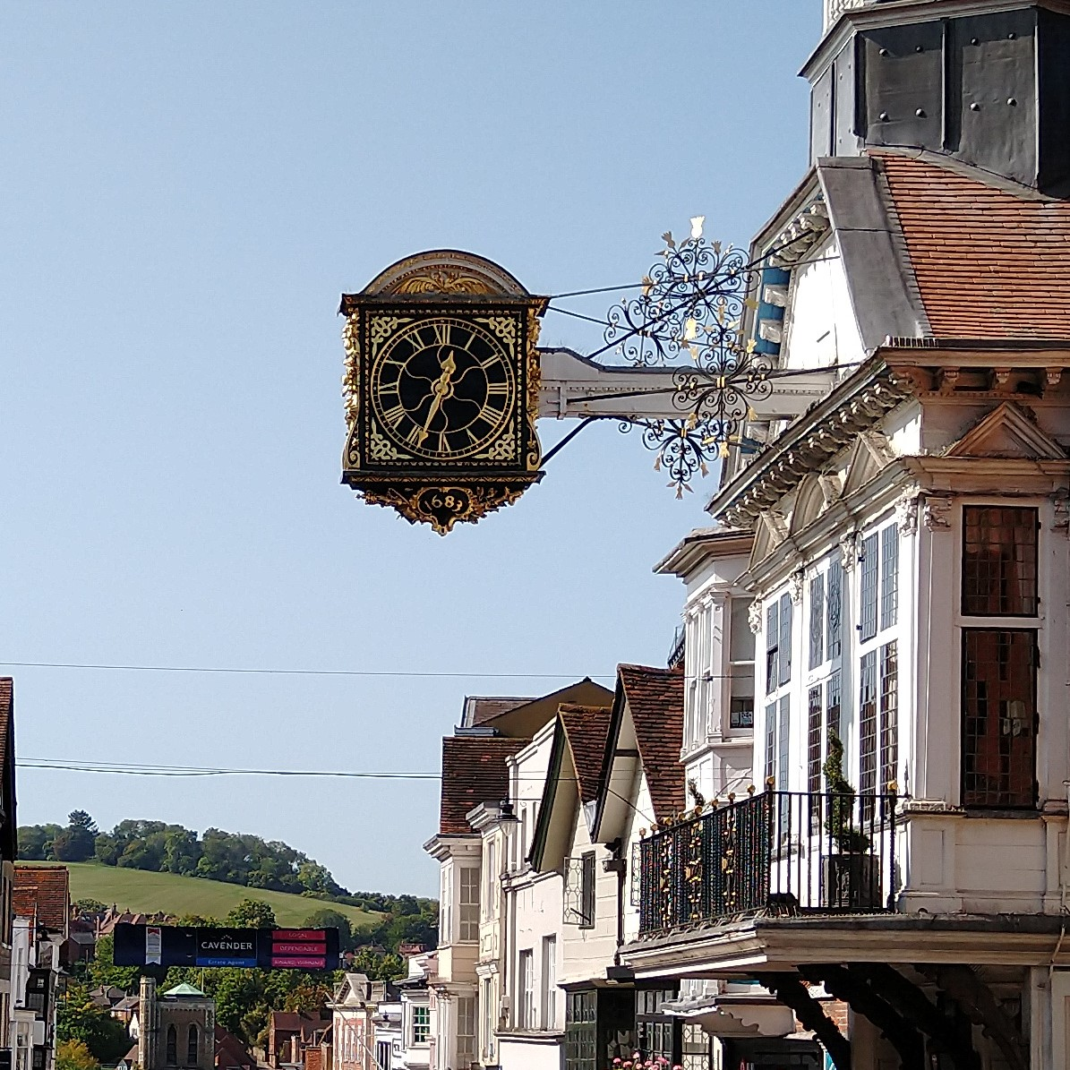 Guildford's famous Guildhall clock on the High Street with the Hog's Back in the background.