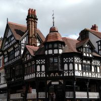 The famous Chester Rows, continuous, half-timbered galleries, which form rows of shops above those at street level. These are on the corner of Bridge Street and Eastgate Street.
