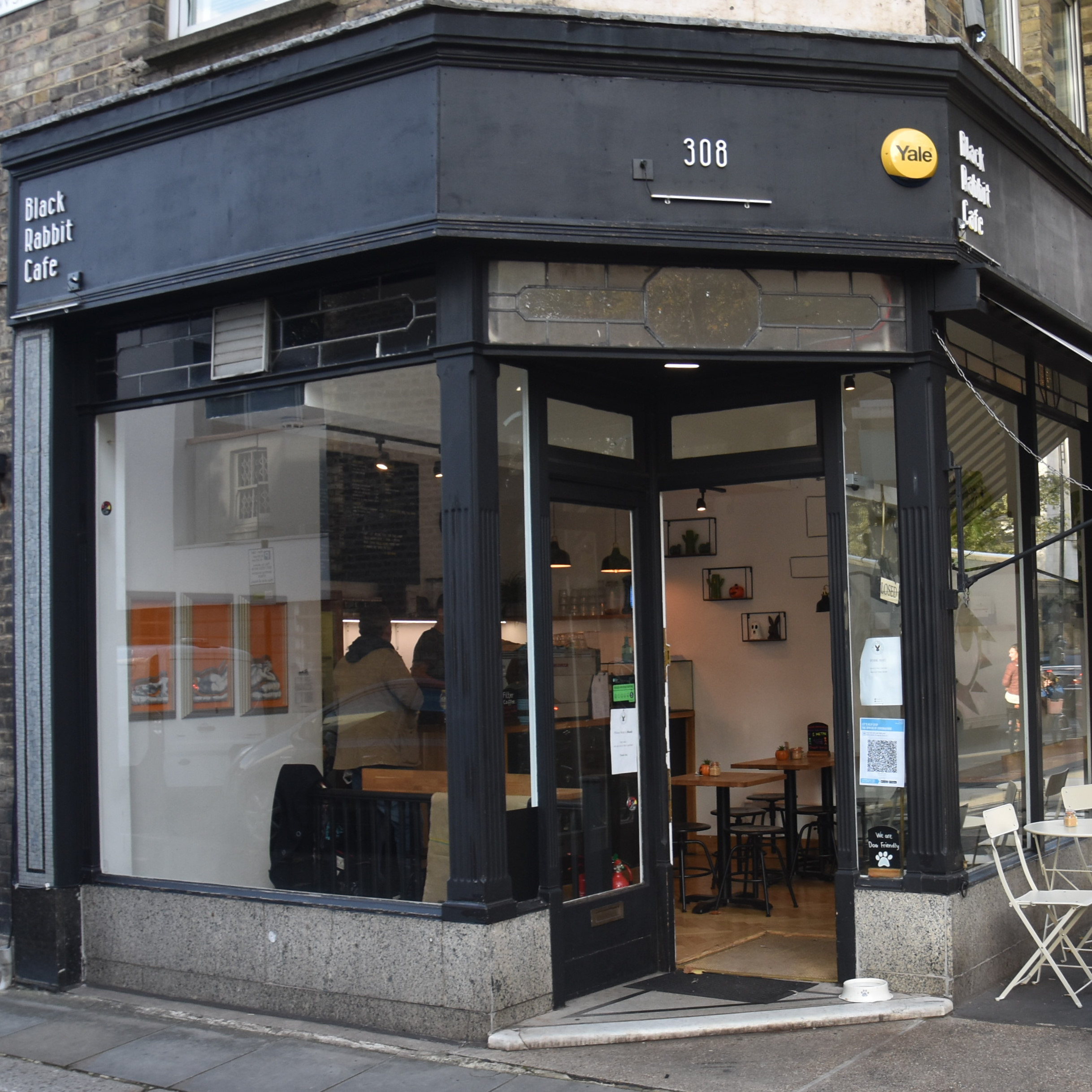 Black Rabbit Speciality Coffee on the corner of the street, the door recessed in a cut-away at 45° to the windows.