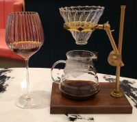 The coffee service at Queens of Mayfair, with a V60 on a brass stand, and a large wine glass to the left of that.