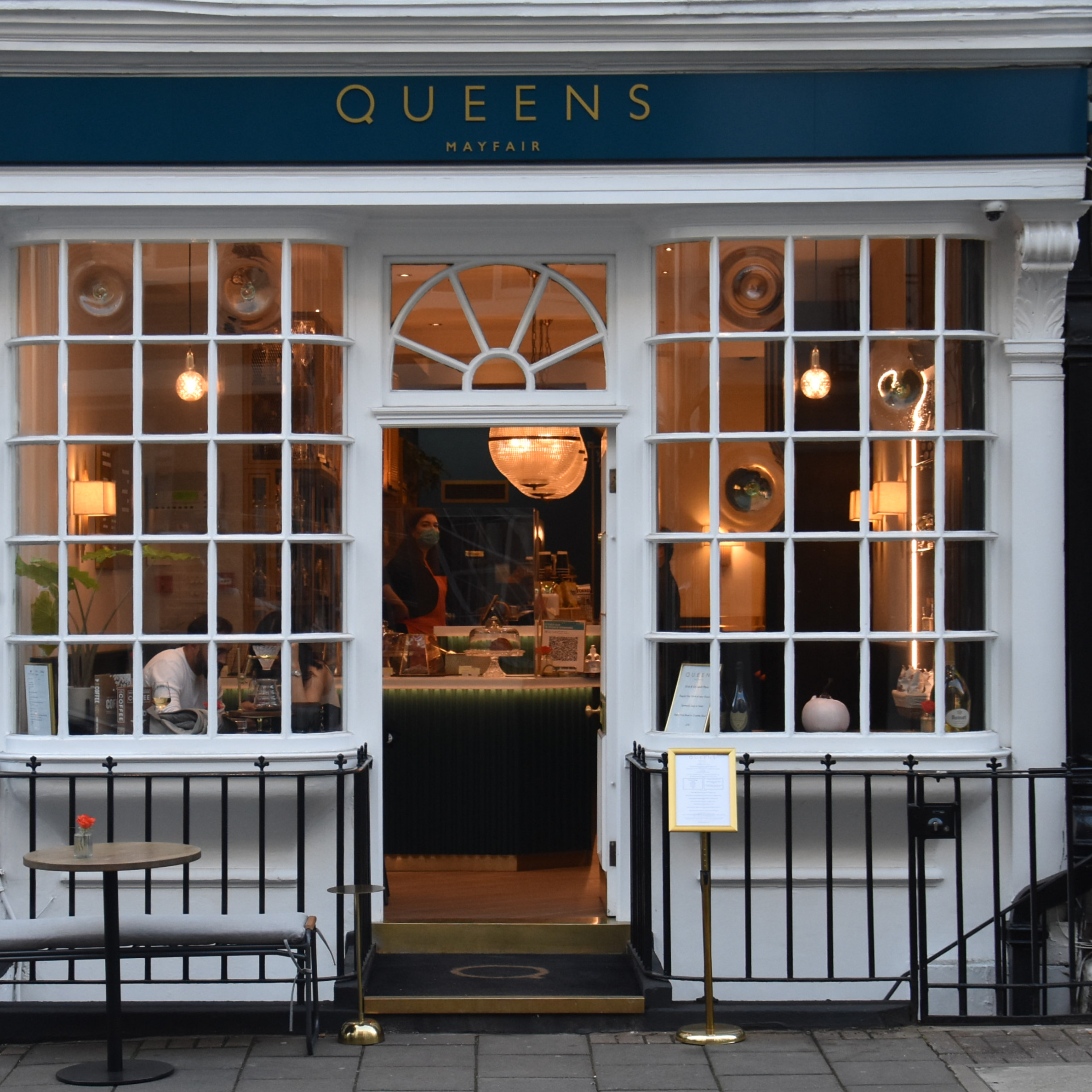 The unassuming façade of Queens of Mayfair, the central door flanked by two tall, square-paned bay windows. There's also a table on the pavement in front of the window to the left of the door.