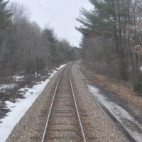 The view from the final carriage of Amtrak's Adirondack service on its way from New York City to Montréal in March 2013, looking back over the single track as it passes through woods north of Albany.