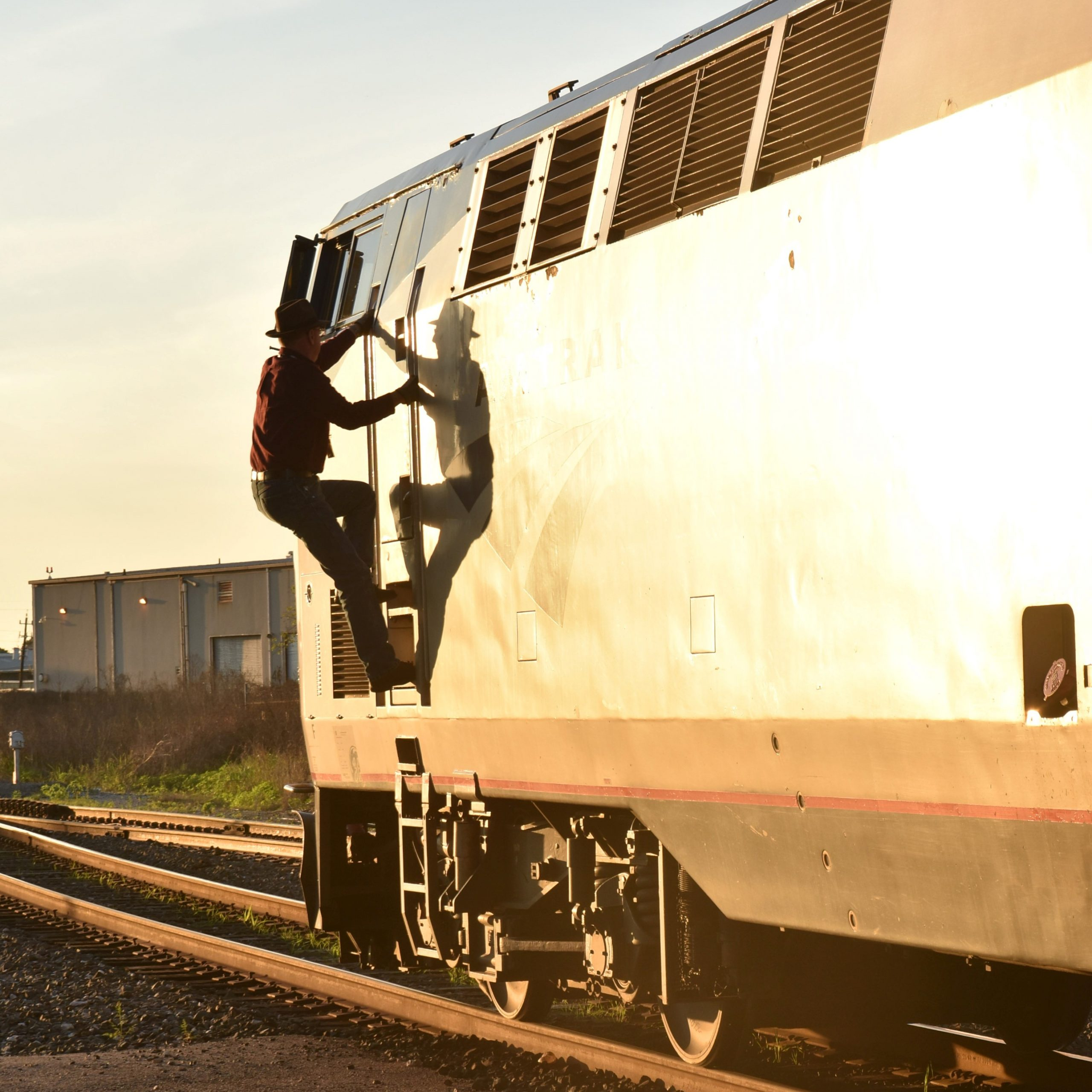 The driver climbing up in the evening sun to get into the cab of the lead locomotive of the Sunset Limit at Houston, Texas