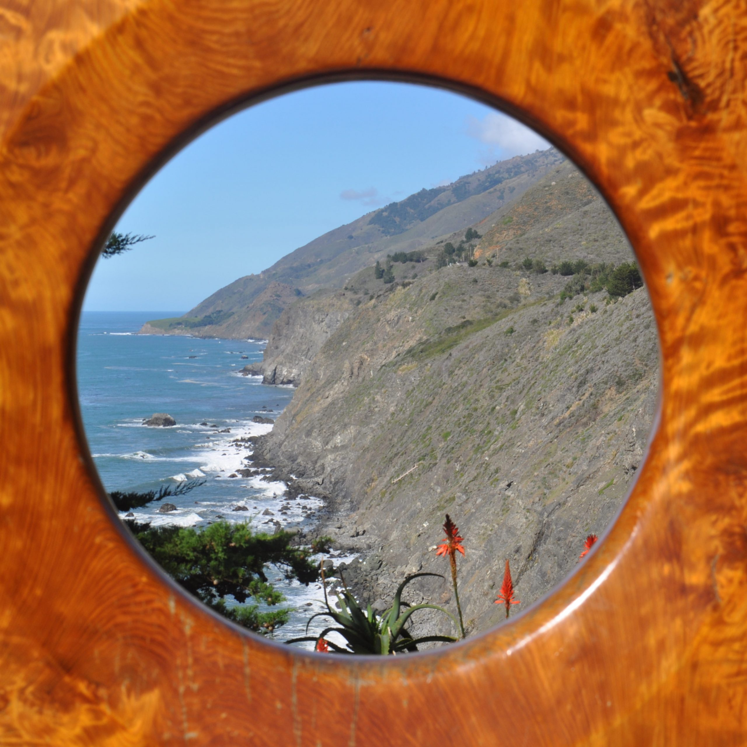 """A view through the """"Portal on the Big Sur"""" at Ragged Point Inn, looking north along the coastline."""