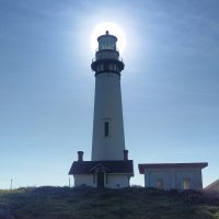 The sun, directly behind the lighthouse at Pigeon Point, on the California coast, south of San Francisco.