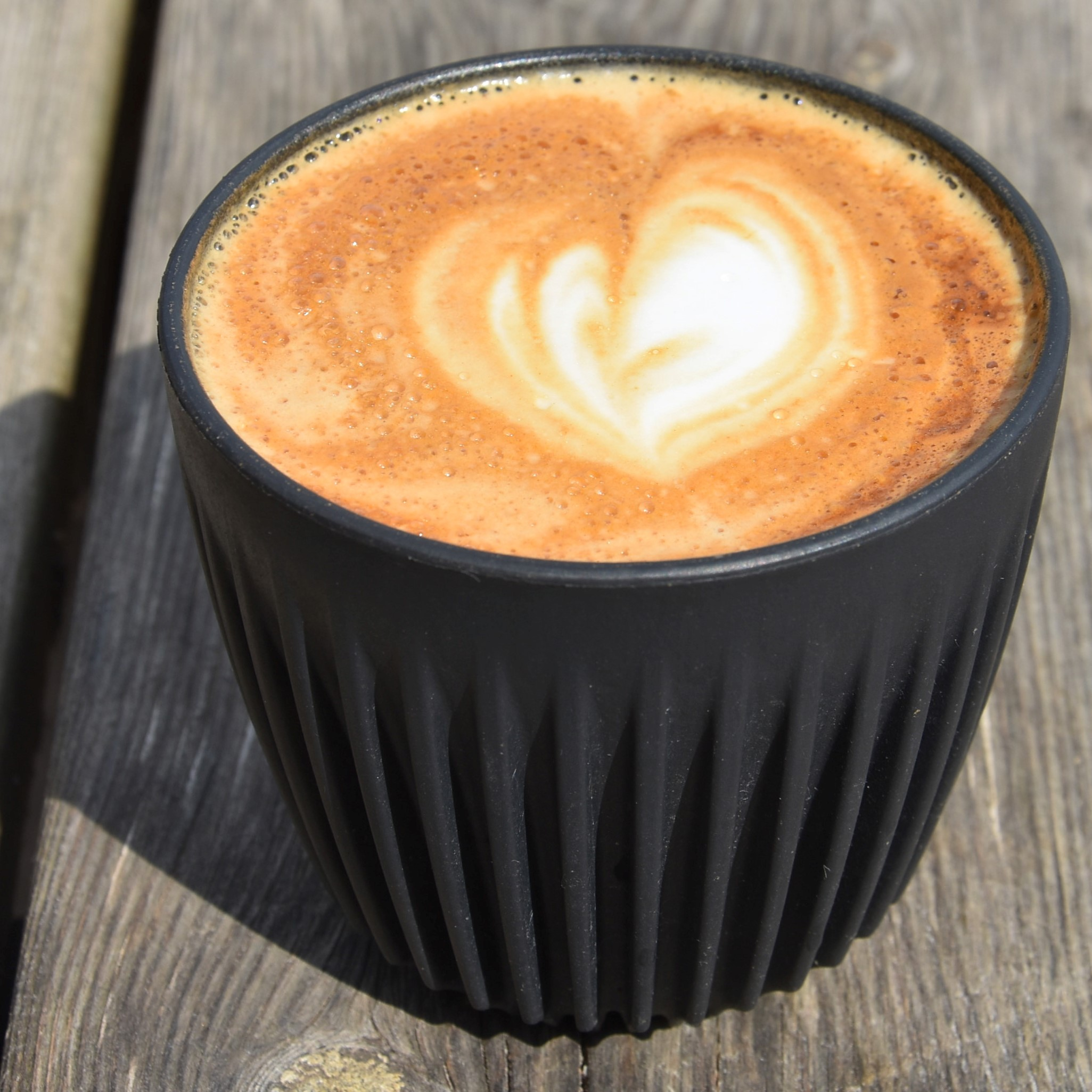 Coffee in the sun: my flat white, in my HuskeeCup, sitting in the sun in the farmyard at Espresso Farm.