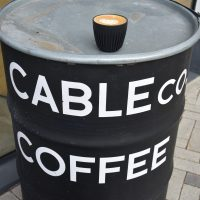 My decaf flat white on my HuskeeCup, sitting on an old barrel outside Cable Co. in The Aircraft Factory.