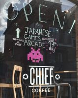 The front window of Chief Coffee celebrating the opening of the Japanese games arcade on the top floor.
