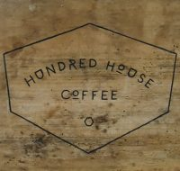 The words Hundred House Coffee, surrounded by an irregular hexagon, carved in black on wood.