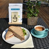 My brie and cranberry sandwich, along with my flat white, sitting in the sun on the patio at Open Grounds Café.