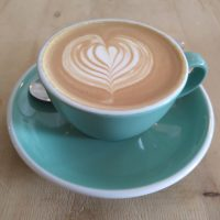 A lovely flat white, served in a blue cup, made with the Housemartin blend at Wylde Coffee.