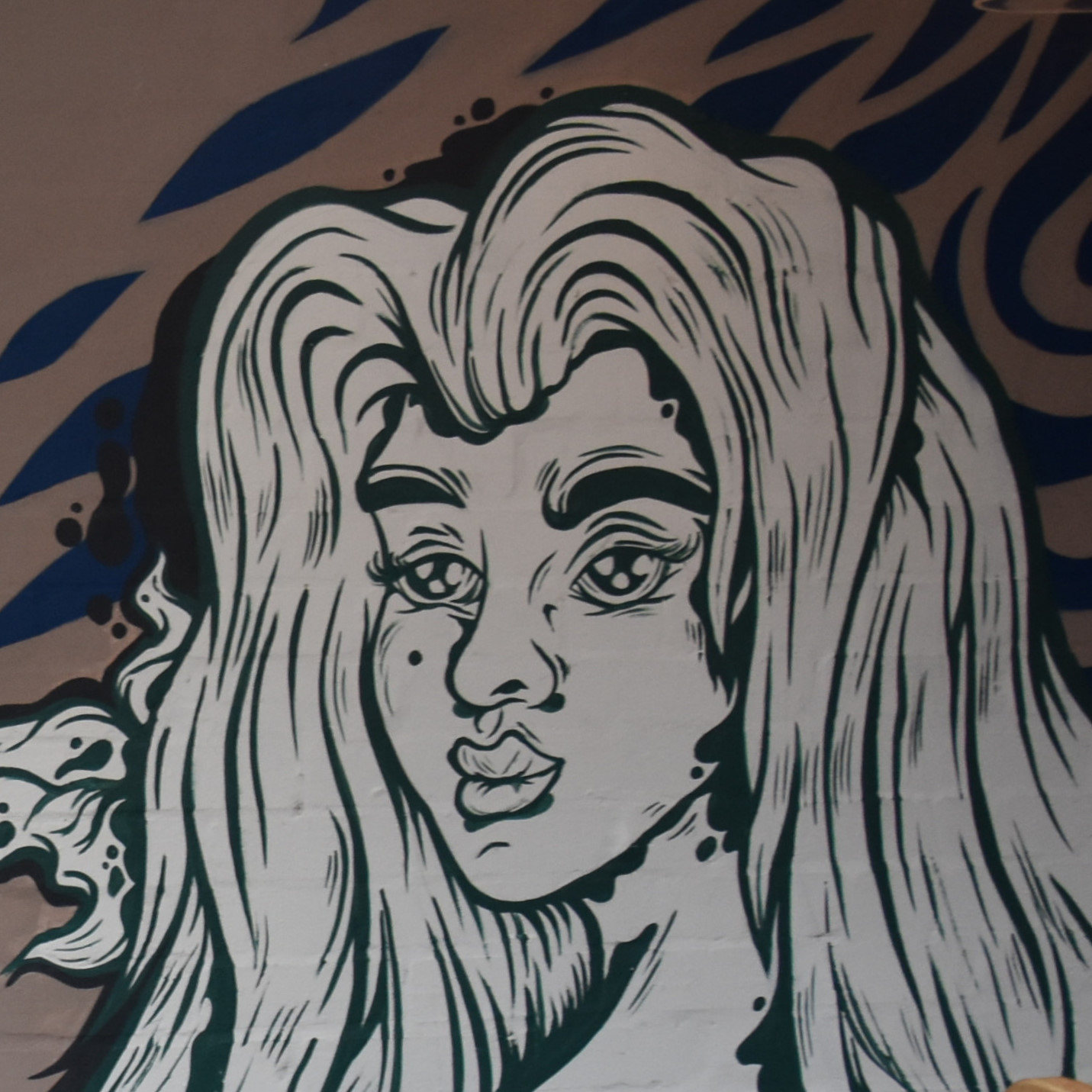 Artwork from the upstairs wall of one of the new rooms in Liar Liar, the head of woman with long, wavy hair in a black and white line drawing.