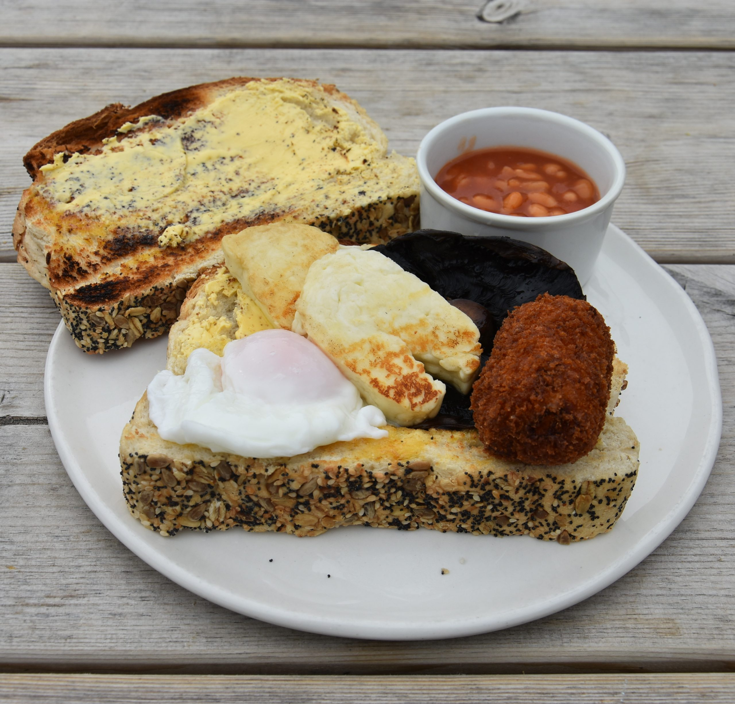 My Vegetarian Stacked breakfast at the Riverbanc in Llangollen: egg, halloumi, mushrooms, croquette, beans and seeded toast (plus an extra slice).