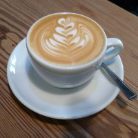 A flat white, with some lovely latte art, served in a classic white cup at Sam's Coffee in Llangollen.