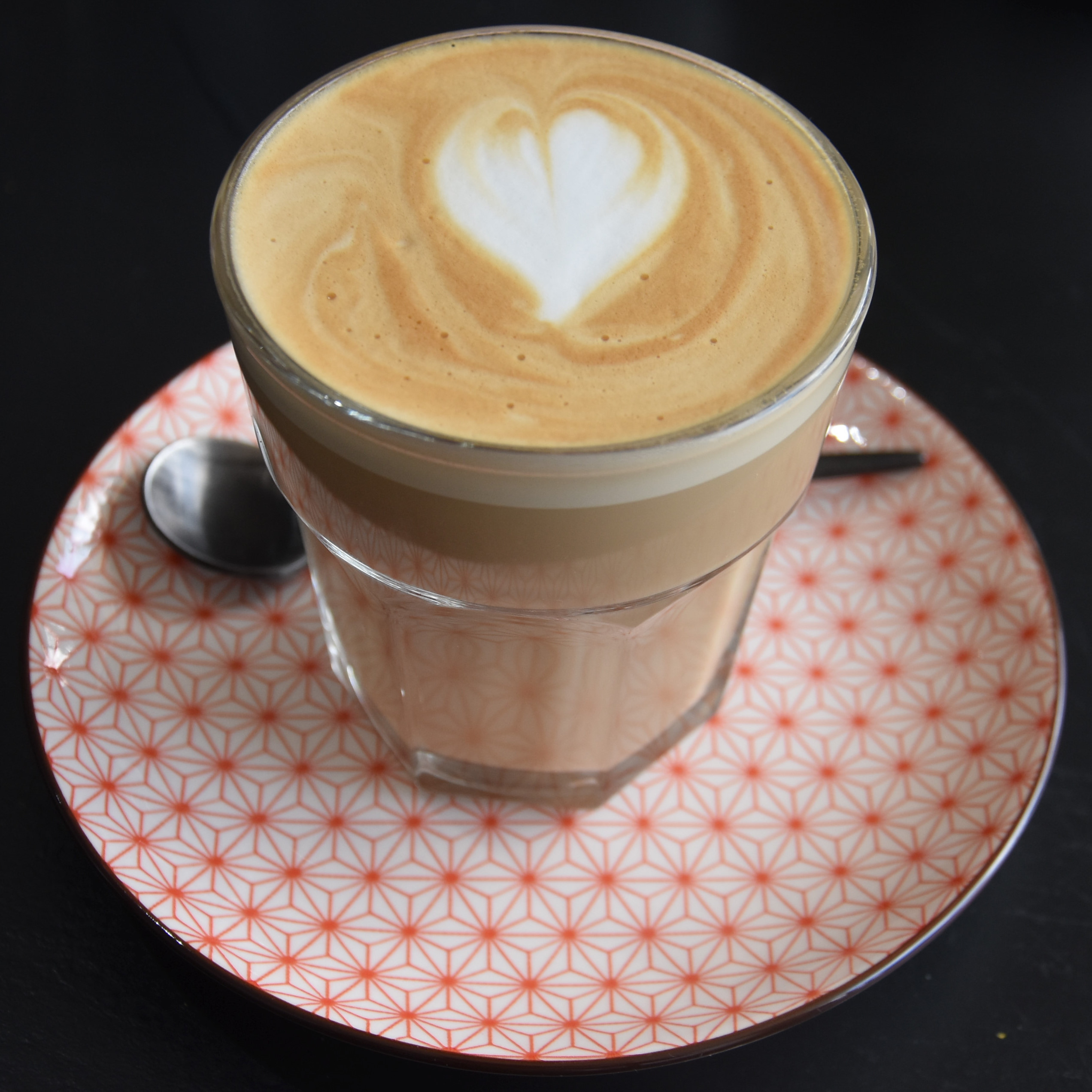 A lovely flat white, made with the Trio blend from Crosby Coffee and served in a glass on a geometrically patterned saucer at Ginger Monkey in Chester.