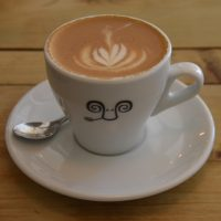 A decaf flat white, made with Oato oat milk, and served at Jaunty Goat in Chester, in a classic white tulip cup.