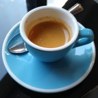 An espresso, made with Kiss the Hippo's Bensa from Ethiopia, an anaerobic natural with tasting notes of blackberry, pineapple and strawberry jam, served at Nostos in a classic blue cup.
