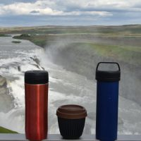 Our Espro Travel Presses (mine, in red, on the left, Amanda's, in blue on the right) overlook the Gullfoss waterfalls in Iceland, with my HuskeeCup sandwiched between them.